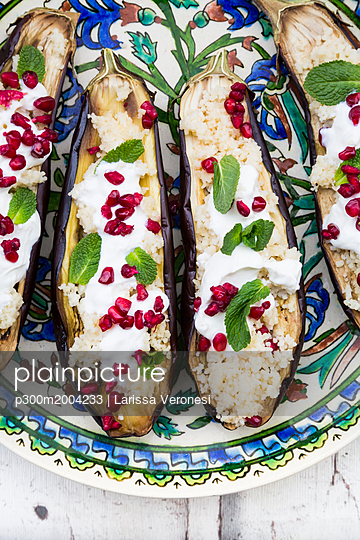 Filled aubergines with couscous, yogurt sauce, mint and pomegranate seeds - p300m2004233 von Larissa Veronesi