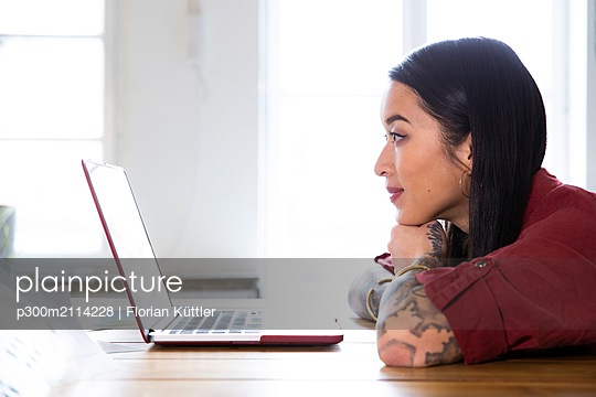 Woman using laptop at table in office - p300m2114228 von Florian Küttler