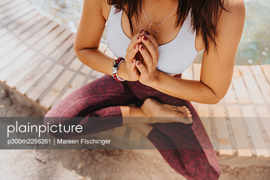 Mature athlete doing yoga while sitting with hands clasped and cross-legged at park - p300m2256261 by Mareen Fischinger