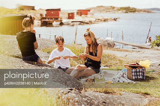 Mother making craft with children by harbor during summer vacation - p426m2238140 by Maskot