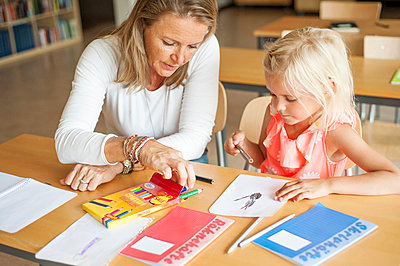 Teacher assisting girl in choosing color pencils during art class - p1185m994143f by Astrakan
