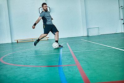 Man playing indoor soccer shooting the ball - p300m1587569 von Zeljko Dangubic