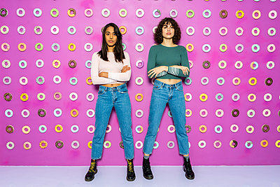 Two young women posing at an indoor theme park with donuts at the wall - p300m2102194 by VITTA GALLERY