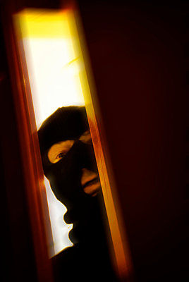 Mans wearing balaclava opening door - p597m793877 by Tim Robinson