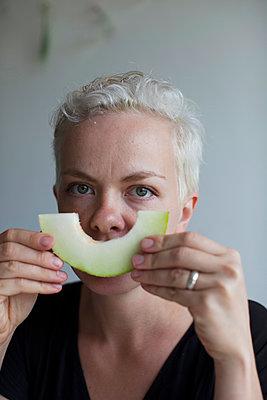 Frau hält eine Melonenscheibe - p906m1362774 von Wassily Zittel