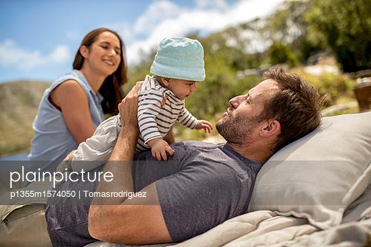 Familie mit Baby entspannt sich am Seeufer - p1355m1574050 von Tomasrodriguez