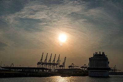 Containerhafen und ein Kreuzfahrtschiff bei Sonnenuntergang - p229m1574854 von Martin Langer