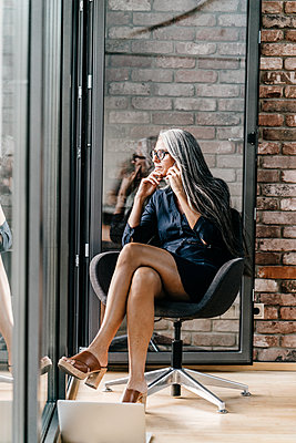 Woman with long grey hair on cell phone sitting at the window - p300m1192066 by Kniel Synnatzschke