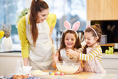 Happy mother and daughters baking Easter cookies in kitchen together - p300m1567650 by gpointstudio
