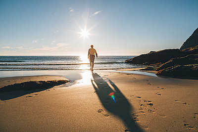 Norway, Lofoten, Moskenesoy, Man walking into the sun at Kvalvika Beach - p300m2004640 von Gustafsson