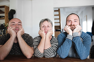 Portrait of adult sons with senior mother sitting at table at home with head in hands - p300m2103385 by Katharina Mikhrin
