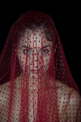 Young woman under transparent red veil - p427m1195676 by Ralf Mohr