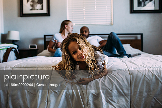 young girl playing on the end of the bed with parents in background - p1166m2200244 by Cavan Images