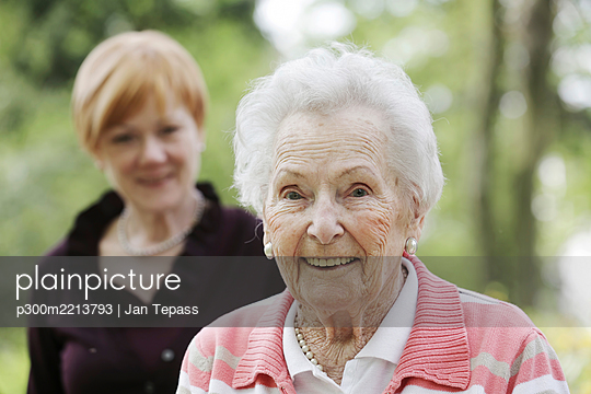 Germany, North Rhine Westphalia, Cologne, Portrait of senior woman smiling while mature woman in background - p300m2213793 by Jan Tepass