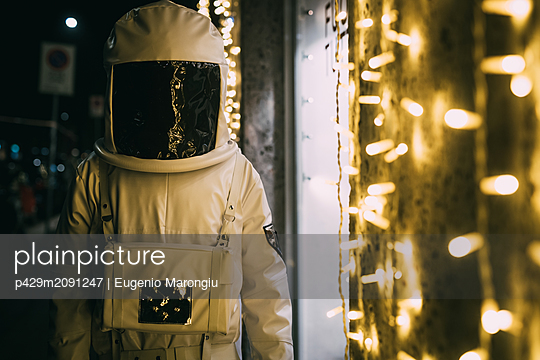 Astronaut standing in front of illuminated shopfront - p429m2091247 by Eugenio Marongiu