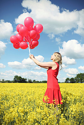 Woman with red balloons - p045m945602 by Jasmin Sander