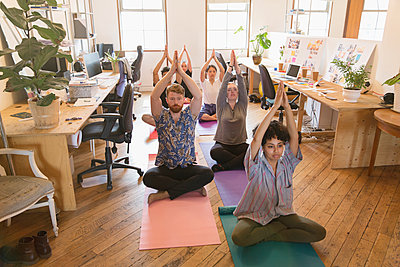 Creative business people practicing yoga in office - p1023m2016713 by Tom Merton