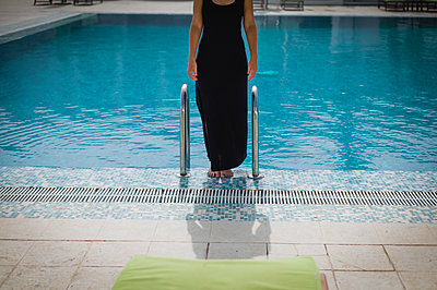 Woman in black dress standing by a poolside - p1150m2134460 by Elise Ortiou Campion