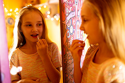 Girl looking in the mirror and applying red lipstick - p1315m2041482 by Wavebreak