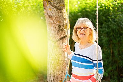 Happy woman sitting on swing in garden - p300m2253215 by Annika List