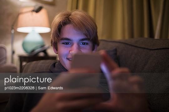 Smiling teenage boy using smart phone on living room sofa - p1023m2208328 by Sam Edwards
