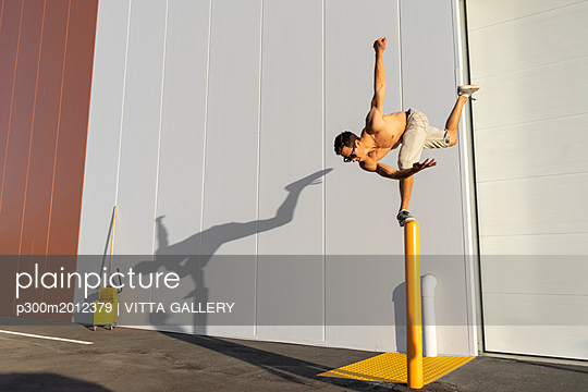 Acrobat training on a pole - p300m2012379 von VITTA GALLERY