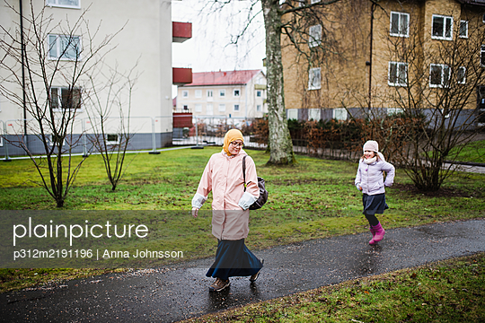 Mother with daughter walking together - p312m2191196 by Anna Johnsson