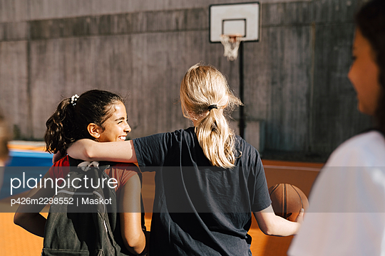 Blond girl with arm around female friend while walking in basketball court - p426m2298552 by Maskot