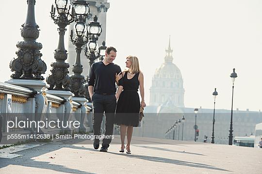 Caucasian couple walking on urban bridge - p555m1412638 by Smith Photographers