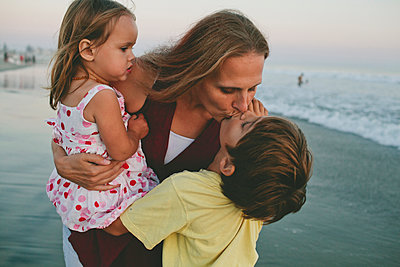 Mother kissing son while carrying daughter on shore at beach - p1166m1508288 by Cavan Images