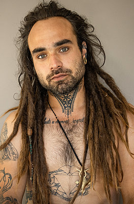 Young man with long hair and lots of tattoos - p1640m2245803 by Holly & John