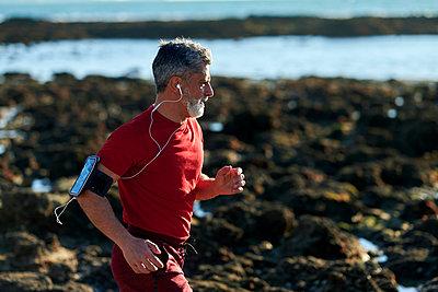 Man with headphones running on beach - p300m2275705 by Kiko Jimenez