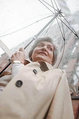 Mature woman holding umbrella on rainy day - p300m2276719 by Katharina und Ekaterina