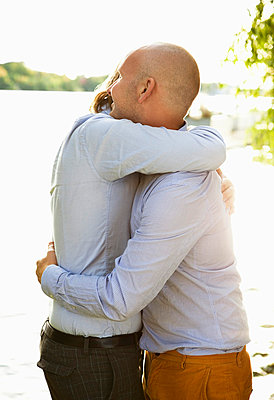 Two gay men hugging by the water\\\'s edge - p4265763f by Maskot