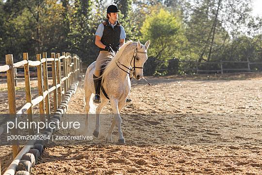 Man riding horse on riding ring - p300m2005264 von zerocreatives