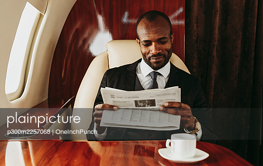 Young businessman reading newspaper while traveling in airplane - p300m2257068 by OneInchPunch