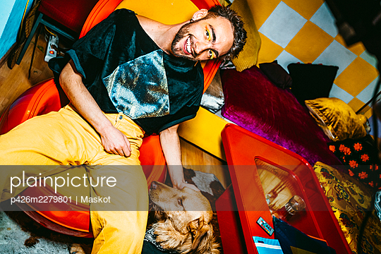 Portrait of smiling young man with dog in living room - p426m2279801 by Maskot