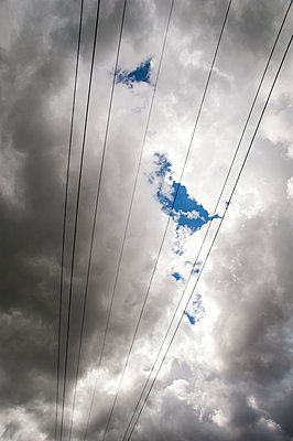 Power lines against clouds - p1047m1475145 by Sally Mundy
