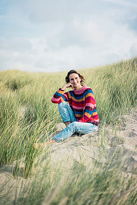 Mature woman relaxing on the beach, sitting in the dunes - p300m2059255 von Robijn Page