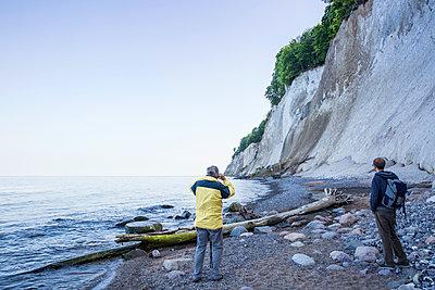 Germany, Mecklenburg-Western Pomerania, Ruegen, Jasmund National Park, hikers looking on chalk cliff at 'Kieler Ufer' - p300m2059317 von Maria Maar