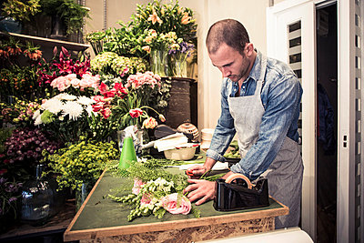 Mid adult male florist preparing bouquet of flowers at desk in shop - p426m811505f by Maskot