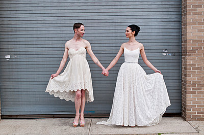 Gender fluid model and female model showing off cotton wedding dresses - p429m1158519 by Angela Cappetta