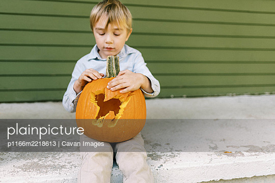 Little boy sitting on his porch showing off carved halloween pumpkin - p1166m2218613 by Cavan Images