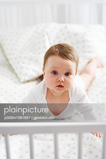 Portrait of baby lying in crib - p300m1581651 von gpointstudio