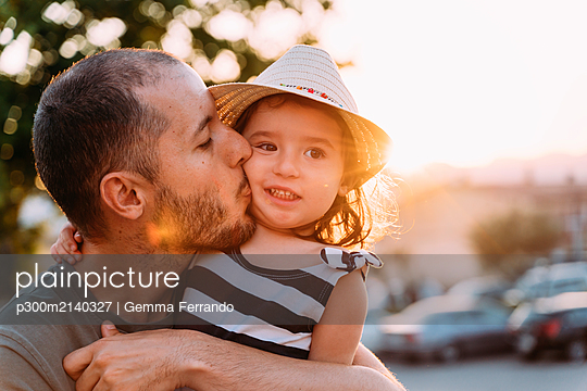 Father kissing his little daughter at sunset - p300m2140327 by Gemma Ferrando