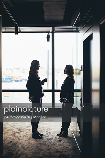 Side view of female coworkers discussing while standing at workplace - p426m2205070 by Maskot