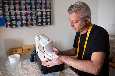a tailor working with his sewing machine in his small workshop set up - p1166m2279604 by Cavan Images