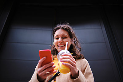 Smiling young woman with smoothie using smart phone near black door - p300m2290464 by Angel Santana Garcia
