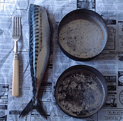 Filleted fish on newspaper with vintage style cookware - p349m695187 by Emma Lee