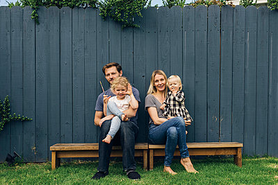 Full length portrait of parents and children sitting on seats against fence at yard - p426m1451755 by Maskot